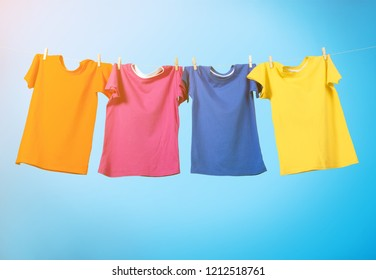 Colorful T-shirts hanging on a rope on a white background