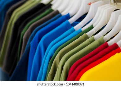 Colorful t-shirts on hang for sale in shop. Multicolored summer top on hanger. Summer season clothes department store. Unisex apparel for warm weather. Summer sale in shopping mall. Rainbow tshirts