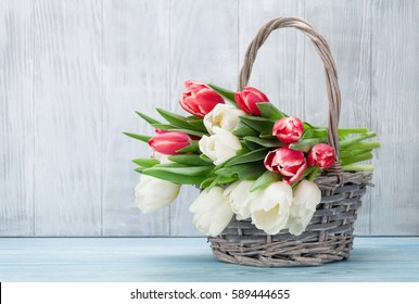 Colorful tulips bouquet basket in front of wooden wall. Easter card. With space for your greetings