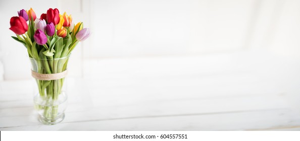 Colorful tulips in a glass vase for mothers day or wedding on a white wooden table in vintage style