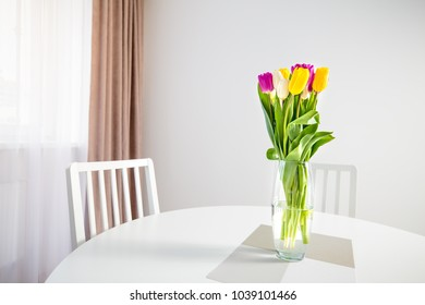 Colorful tulips on table on white wall background. Spring flowers in tall vase near window.