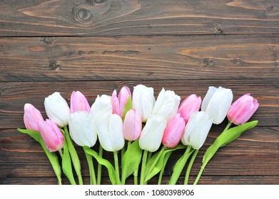 Colorful tulips on wooden background.