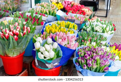Colorful tulips, roses and other flowers in pots at entry to small flower shop