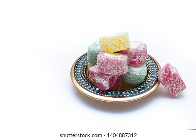 Colorful Turkish delight (aka lokum) in traditional bowl isolated on white background with copy space for your text. Middle Eastern dessert popular in the month of Ramadan.