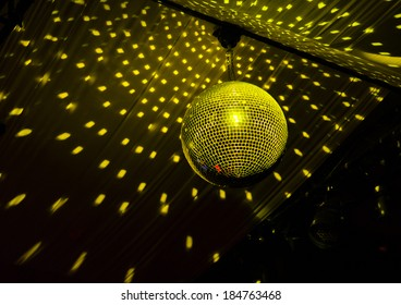 Colorful turquoise blue mirrored metallic disco ball in a nightclub hanging in the darkness with copyspace