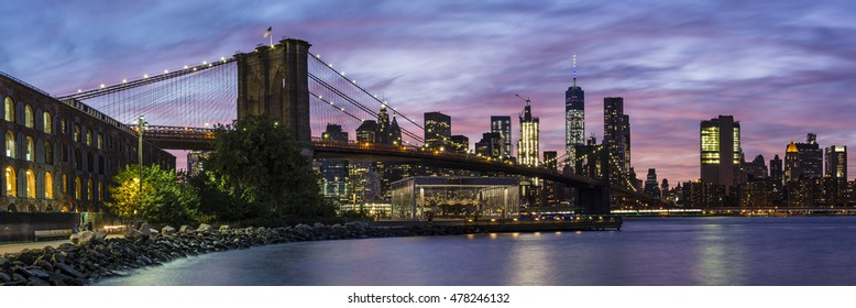 A colorful twilight view of the Brooklyn Bridge, Jane's Carousel and the Manhattan skyline see from Empire Fulton Ferry Park in Brooklyn. NY