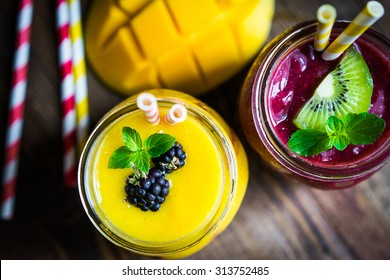 Colorful two layer smoothies with mango and berries on rustic wooden background