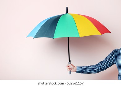 Colorful umbrella in male hand on beige background