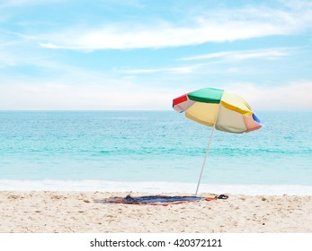 Colorful umbrella and mat on summer sand beach