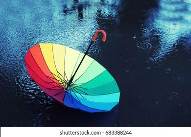colorful umbrella in rain. autumn background concept. multicolored umbrella in puddle, rainy weather. fall time. rainy season. copy space