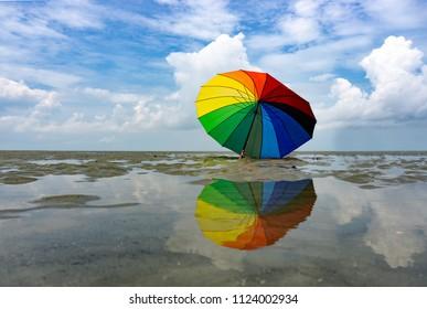 Colorful umbrella and reflection at Sasaran beach in Kuala Selangor, Malaysia.