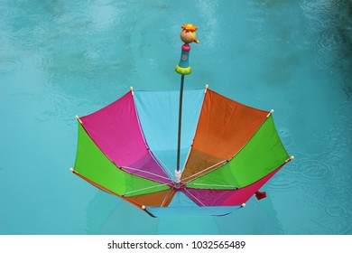 Colorful umbrella with wooden doll handle floating in azure blue pool in rain