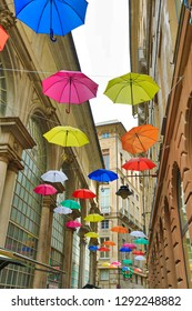 Colorful umbrellas adorn a street in downtown Genoa (Genova), Italy.  This is a popular attraction for tourists.