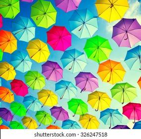 Colorful umbrellas background. Colourful umbrellas urban street decoration. Hanging Multicoloured umbrellas over blue sky. Bright Colors backdrop
