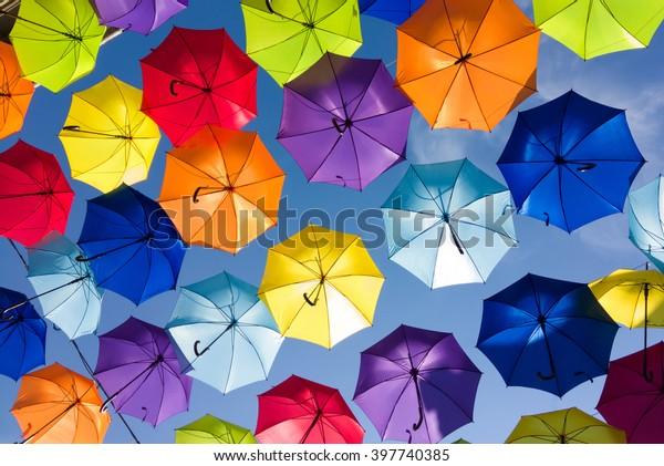 Farbiger Hintergrund. Farbige Regenschirme am Himmel. Straßendekoration.