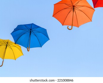 Colorful umbrellas floating against a blue sky