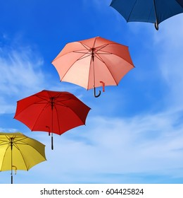 Colorful umbrellas flying into blue sky background