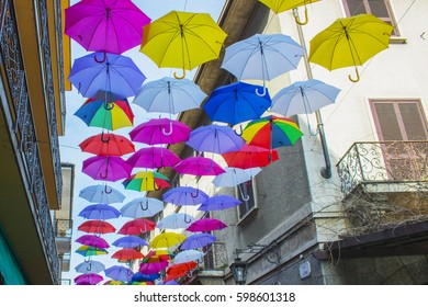 Colorful umbrellas hanging above street of Arona, Italy