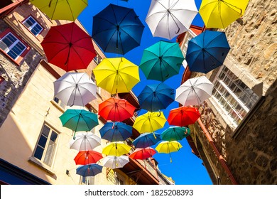 Colorful umbrellas hanging over a street in old Quebec city in a sunny day, Canada