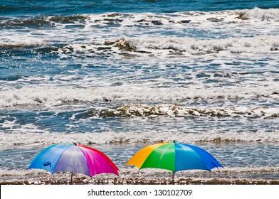 Colorful umbrellas on beach with breaking ocean waves