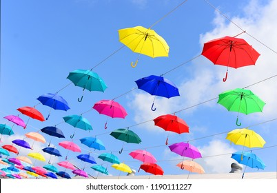 Colorful umbrellas over bright blue sky background.