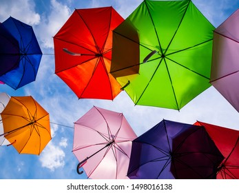 Colorful umbrellas with the sky in background. Walkway and street decoration.