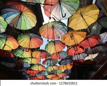 Colorful umbrellas under the city street in Paris, joyful mood of multi colored umbrellas in Istanbul, colorful umbrellas under the roof top on the street in Berlin