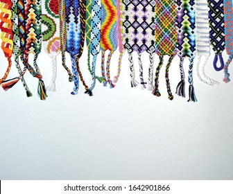 Colorful unique friendship bracelets made of thread with braids on white background with copy space