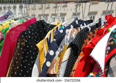 Colorful used blouses on hangers at open air second hand market