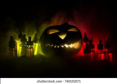Colorful vape liquids with Halloween pumkin on dark background. Vape Halloween party or vape promo concept on Halloween holidays promo