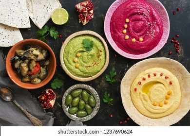 Colorful varied hummus, caponata, olives, pita and pomegranate on a dark rustic background. Vegetarian diet food.Top view, flat lay. Mediterranean food