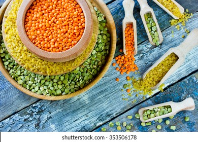 Colorful variety of cereals in a bowls and scoops on wooden background. Red lentils, yellow bulgur and green dried peas
