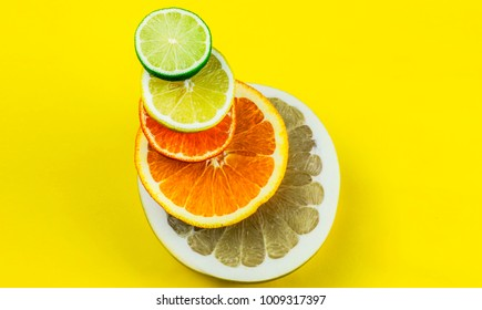 Colorful variety of citrus fruits on a bright yellow background. Top view image