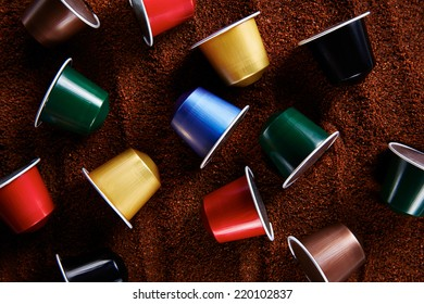 Colorful variety of coffee capsules on coffee background