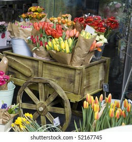 Colorful variety of flowers sold in the market in London. Tulips, daffodils and hyacinths in kraft paper, in buckets on a cart