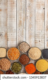 Colorful variety of grains, seeds and nuts on the white wooden table - top view, copy space