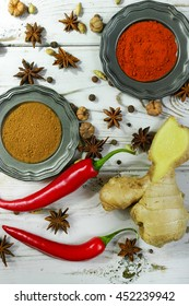 Colorful variety of Indian spices with fresh chili and ginger on white wooden table top