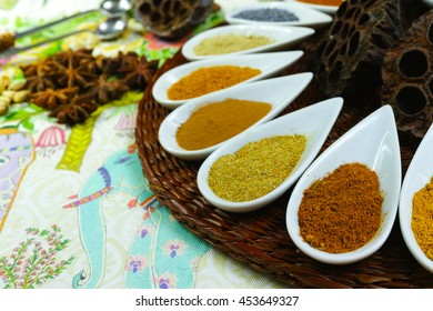 Colorful variety of Indian spices on traditional ornamental background