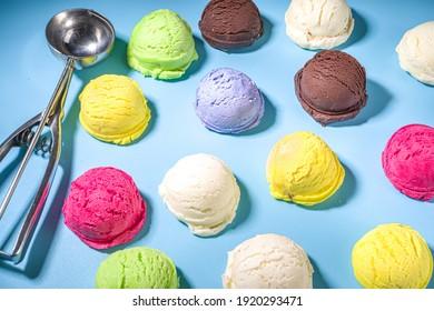 Colorful various ice cream scoops pattern on pastel blue background. Summer minimalism pattern flat lay with hard light. Chocolate vanilla blueberry strawberry pistachio orange ice-cream balls