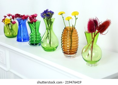 Colorful vases on white table, close-up