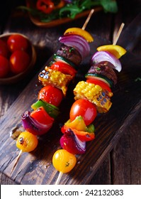 Colorful vegan vegetable skewers with fresh roasted or grilled sweet peppers, onion, mushroom, corn, eggplant and cherry tomatoes, view from above on a wooden board