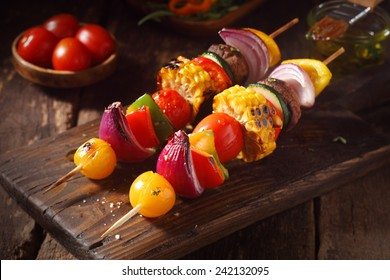 Colorful vegan or vegetarian vegetable skewers with fresh roasted or grilled sweet peppers, onion, mushroom, corn, eggplant and cherry tomatoes, close up view on a wooden board