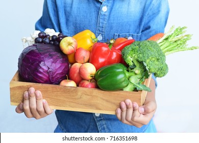 colorful vegetable in wood tray carry by boy hands wear blue jeans shirt, organic garden or healthy clean food vitamin concept with copy space