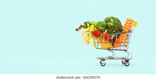 colorful vegetables in the cart on blue background