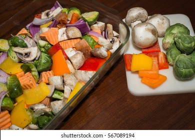 Colorful vegetables cut up and whole on a wood table