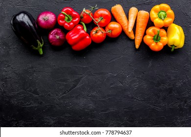 Colorful vegetables for healthy diet. Paprika, tomatoes, carrot, eggplant on black background top view copyspace