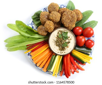 Colorful vegetables, lettuce, falafels on a plate and humus  on a white background.