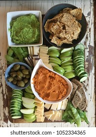 A colorful vegetarian assortment of cheese, hummus, guacamole, olives, fruit, crackers, and bread.