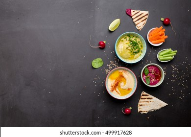 Colorful vegetarian snacks (appetizers) table. Various dips with pita bread. Flat lay composition from above (top view) with free text space on black background. Healthy diet or lifestyle concept.