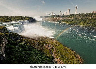A colorful view of the Niagara Falls and rainbow at sunrise